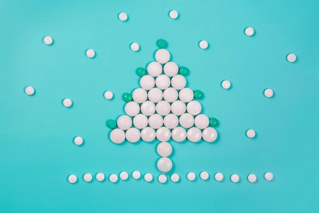 Sapin de noël fait de pilules sur fond bleu. nouvelle année en médecine, pharmacie et parapharmacie.