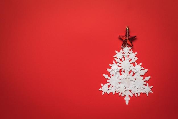 Sapin de noël en flocons de papier blanc avec une étoile rouge sur fond rouge.