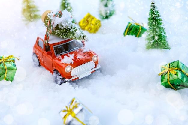 Sapin de noël sur jouet de voiture rouge avec arbre flou et neige. carte de fête de noël
