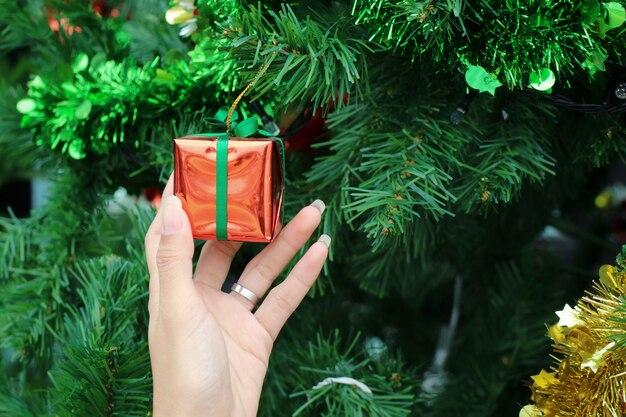Sapin de noël avec main tenant la décoration, vieille boîte cadeau rose. mise au point sélective.