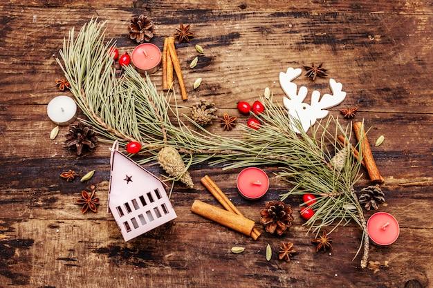 Sapin de noël, maison lumineuse, bougies, épices, cerfs, cônes. décorations nature, planches en bois vintage
