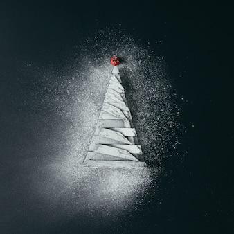 Sapin de noël minimal avec de la neige sucrée sur une surface sombre