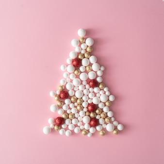 Sapin de noël en or, décoration de boule de paillettes rouge et blanc sur rose. style minimal de fête de carte de voeux de nouvel an. mise à plat. concept de vacances.