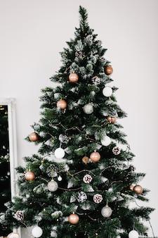 Sapin de noël or décoré dans une pièce blanche. sapin de noël isolé décoré de guirlande. intérieur de la maison d'hiver. fermer.