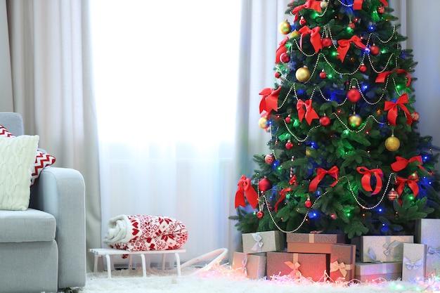 Sapin de noël parfait avec des cadeaux en dessous dans le salon