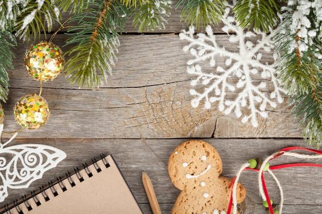 Sapin de noël recouvert de neige, décor et bloc-notes vierge sur fond de planche de bois