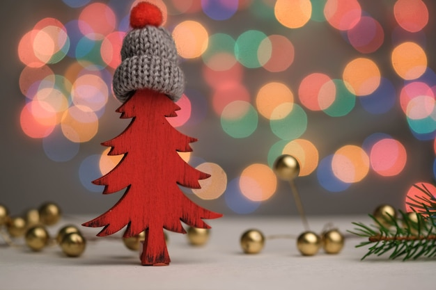 Sapin de noël rouge dans un chapeau, des cadeaux, des boules et une décoration de nouvel an bokeh.
