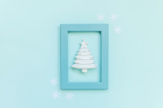 Sapin d'ornement d'objet d'hiver de composition simplement minimale dans un cadre bleu isolé sur bleu pastel