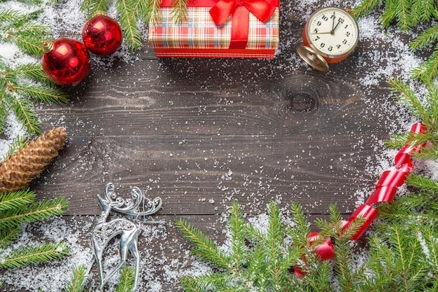 Sapins de noël dans la neige avec cône, horloge vintage, boules de noël, coffret cadeau et cerf sur une planche de bois sombre.