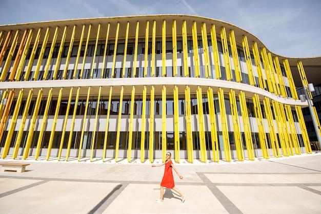 Saragosse, espagne - 21 août 2017 : femme en robe rouge marchant près du pavillon du bâtiment moderne de l'expo 2008, exposition internationale tenue à saragosse, espagne