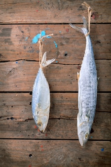 Sardine et barracuda salés suspendus sur un fond en bois ancien.