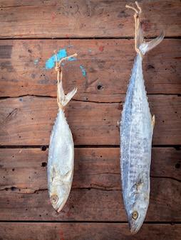 Sardine et barracuda salés suspendus sur le vieux fond en bois