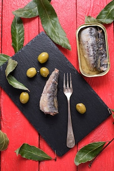 Sardine en conserve sur ardoise et olives avec une table rouge, vue du dessus