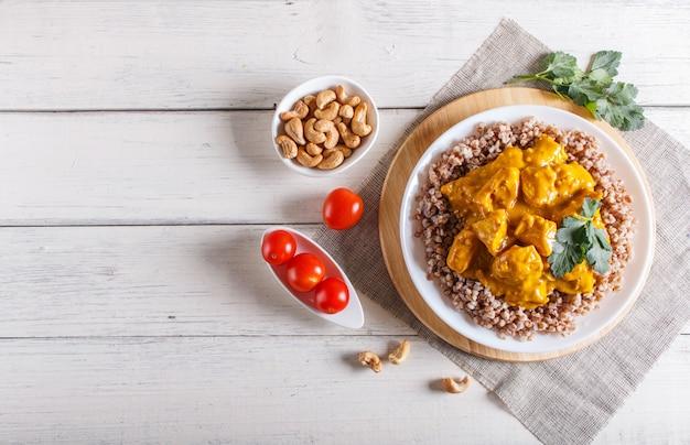 Sarrasin au poulet curry sauce à la noix de cajou sur fond en bois blanc