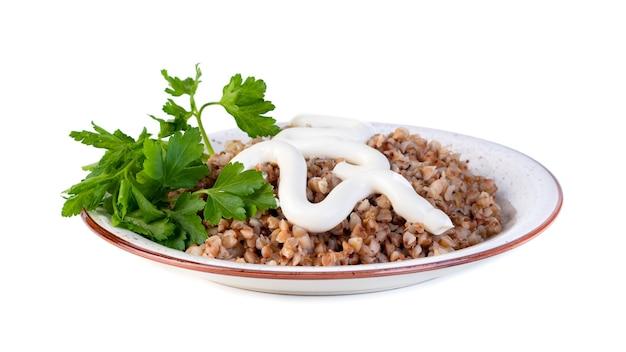 Sarrasin bouilli avec de la mayonnaise et du persil sur une assiette sur une nourriture saine et blanche