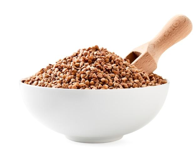 Sarrasin cru dans une assiette avec une cuillère en bois gros plan sur un fond blanc. isolé