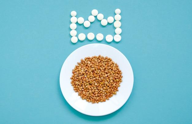 Sarrasin dans une assiette blanche et une couronne de comprimés