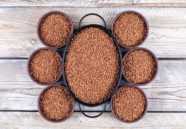 Sarrasin en pot et 6 bols sur un bois blanc. vue de dessus.