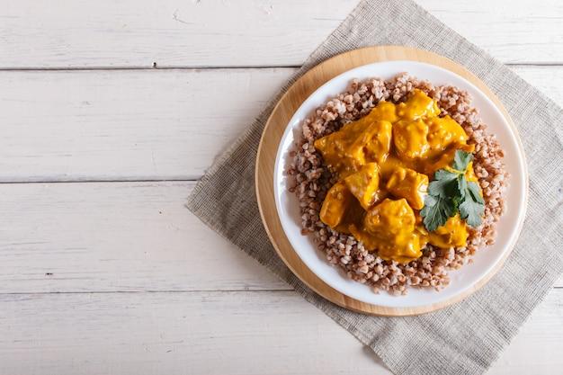 Sarrasin avec sauce au poulet au curry et noix de cajou sur une surface en bois blanche.
