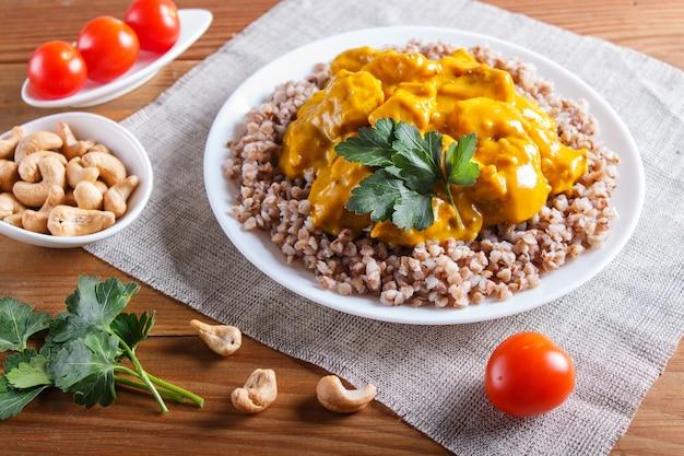 Sarrasin avec sauce au poulet au curry et noix de cajou sur une surface en bois brune.