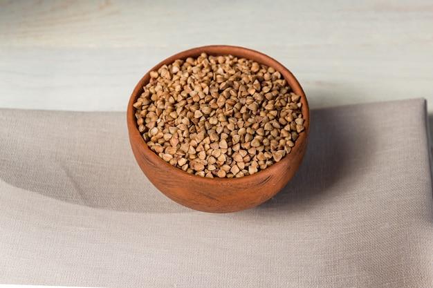 Sarrasin sec dans un bol en argile brune sur une table en bois. céréales sans gluten pour une alimentation saine