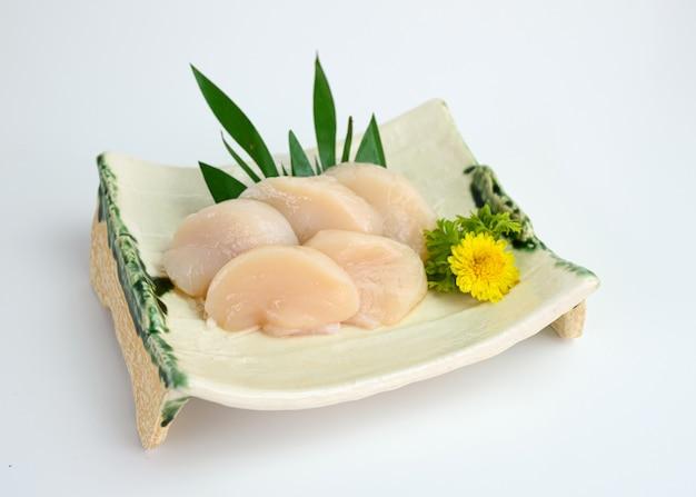 Sashimi de coquille de hotate crue tranchée sur plaque