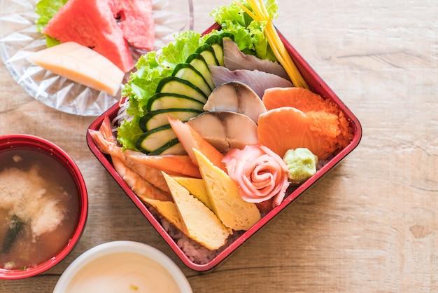 Sashimi frais cru avec du riz dans une boîte à bento
