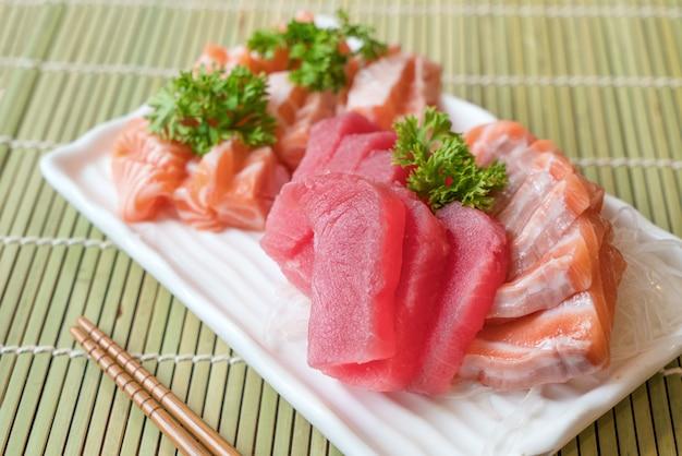 Sashimi de poisson en tranches mélangées sur glace dans une assiette blanche. sashimi saumon et thon set, poisson cru
