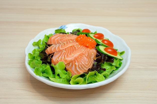 Sashimi de saumon cru aux légumes dans un bol en céramique