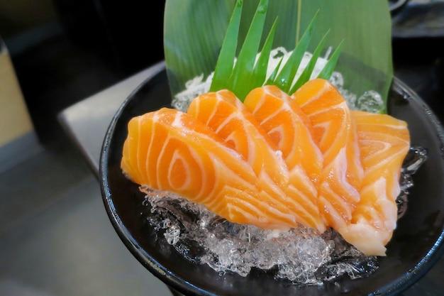 Sashimi de saumon sur glace en plaque noire célèbre nourriture japonaise soft focus. concept alimentaire et décoratif