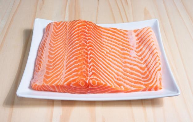 Sashimi de saumon à la japonaise, tranches de filet de saumon cru sur fond noir en bois.