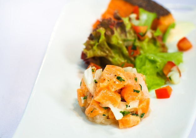 Sashimi de saumon servi avec une salade sur des assiettes blanches.