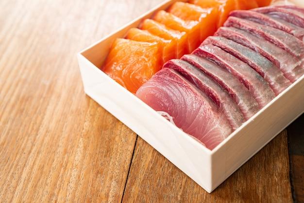 Sashimi de saumon et de thon coupés frais et crus à la japonaise. sur table en bois, manger sainement et bien manger concept. emportez de la nourriture à la maison. fermer