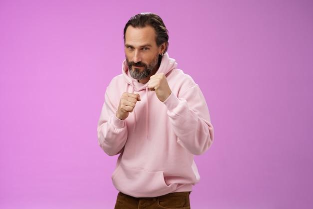 Sassy confiant beau homme barbu caucasien mature en sweat à capuche rose enseignant son fils comment se défendre se défendre lever les poings prêt boxe sourire audacieux, rester en forme, fond violet.