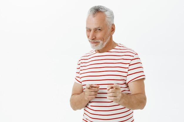 Sassy homme adulte souriant, clignant des yeux et pointant du doigt