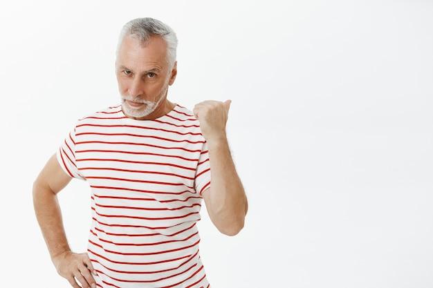 Sassy homme senior sérieux pointant derrière et à la recherche