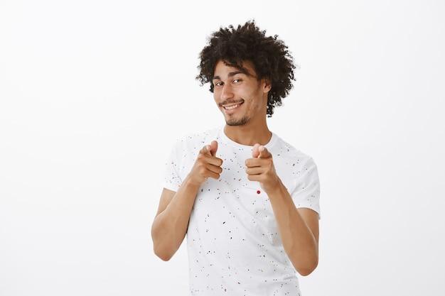 Sassy jeune bel homme pointant du doigt, félicitations geste, louant le bon travail, vous féliciter