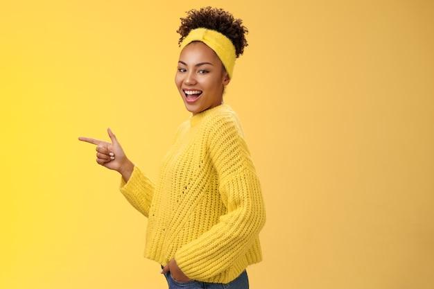 Sassy jolie fille afro-américaine féminine des années 20 en pull bandeau souriante caméra au look coquin et coquin tournant le profil debout pointant vers la gauche introduit un nouveau produit génial montrant la voie, fond jaune.