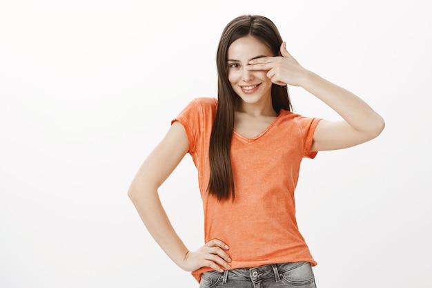 Sassy jolie fille brune souriante et couvrir un œil avec les doigts
