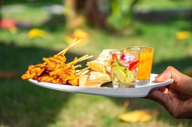 Satay de porc au lait de coco et pain avec une trempette aux arachides sur une assiette en plastique blanche à la main.