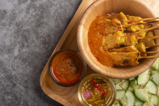 Satay de porc dans un bol en bois recette thaïlandaise.