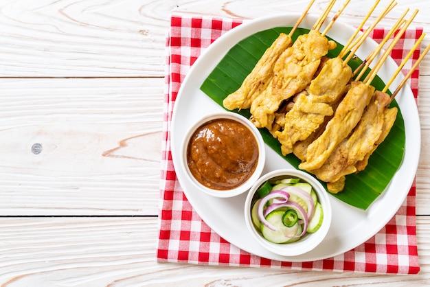 Satay de porc - porc grillé servi avec une sauce aux arachides ou une sauce aigre-douce