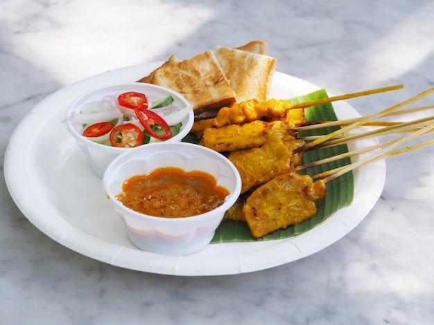 Satay de porc, porc grillé servi avec sauce aux arachides ou sauce aigre-douce