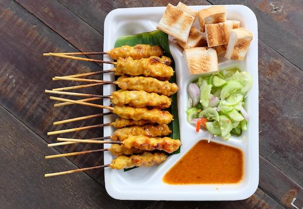 Satay de porc, porc grillé servi avec une sauce aux arachides. vue de dessus.