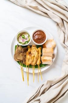 Satay de porc avec sauce aux arachides et cornichons