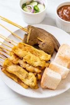 Satay de porc avec votre sauce aux arachides et cornichons qui sont des tranches de concombre et des oignons au vinaigre