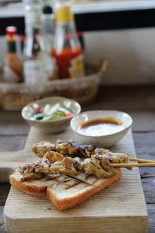 Satay de poulet de cuisine malaisienne avec sauce aux arachides sur fond de bois
