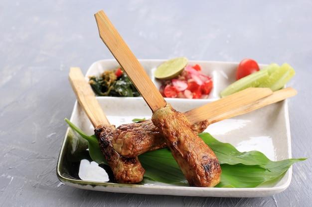 Sate lilit, fruits de mer hachés balinais traditionnels ou satay de poulet avec brochette de bambou. parfois, poursuivant la citronnelle en tant que brochette aromatique. servi sur table avec un autre plat d'accompagnement balinais