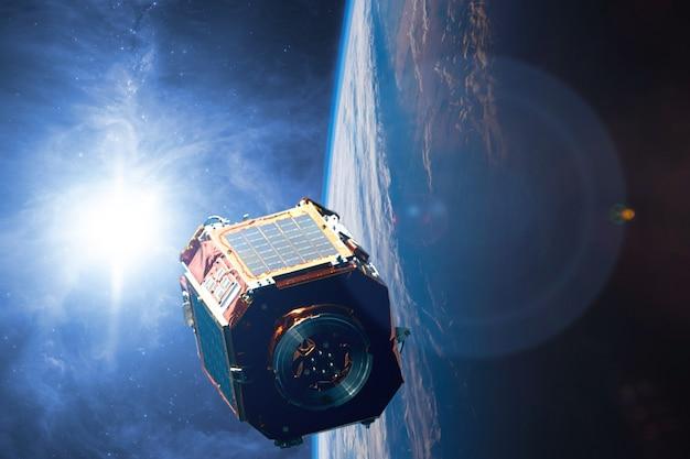 Le satellite dans l'espace au-dessus de la terre est en orbite autour de la planète future technologie b. éléments de cette image fournis par la nasa