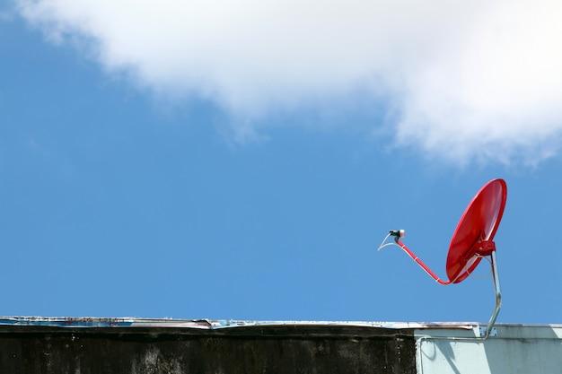 Satellite rouge isolé sur un ciel bleu ensoleillé